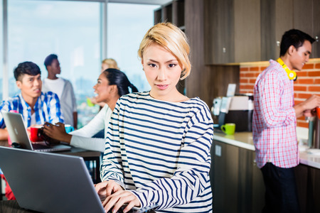 programmer: Chinese woman programmer in lounge of IT start-up with laptop, co-workers in the background