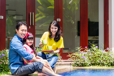 Chinese Family at pool in front of home or house drinking coffee