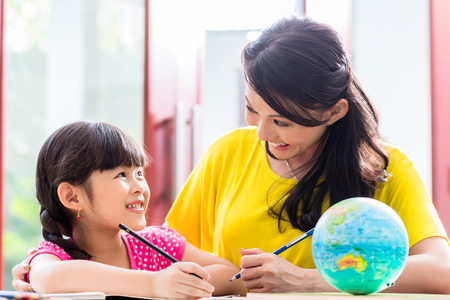 Chinese mother doing school homework with child or homeschooling daughter Stock Photo - 37803446