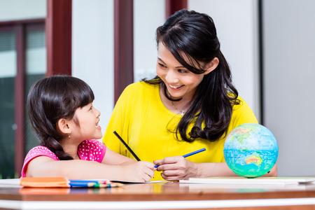 中国人の母親が子供やホーム スクーリングの娘と学校の宿題