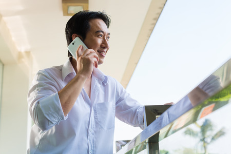 telephoning: Asian man telephoning on home balcony with smartphone