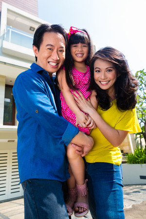 affluent: Asian Chinese family of parents and child standing proud in front of  modern home