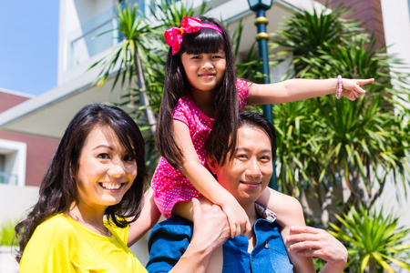 family outside: Asian Chinese family of parents and child standing proud in front of  modern home