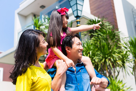Asian Chinese family of parents and child standing proud in front of  modern home