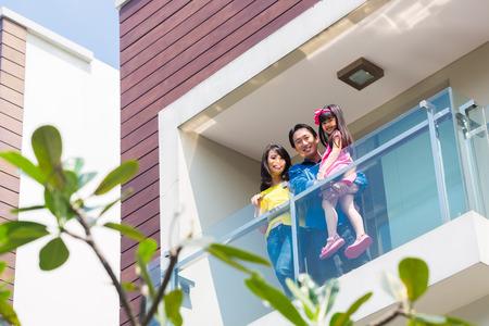 viviendas: Familia china asi�tica de los padres y el ni�o de pie, orgullosos de moderna balc�n casa