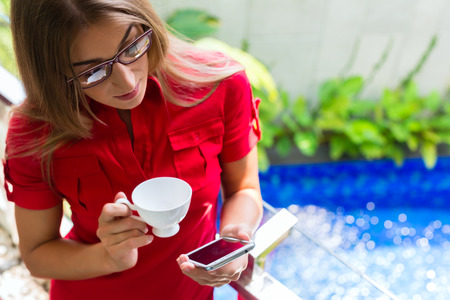 Woman reading Mails on smartphone while drinking coffee on balcony in tropical setting photo