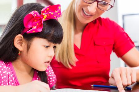 Engels privéleraar helpen Aziatische meisje met huiswerk Stockfoto