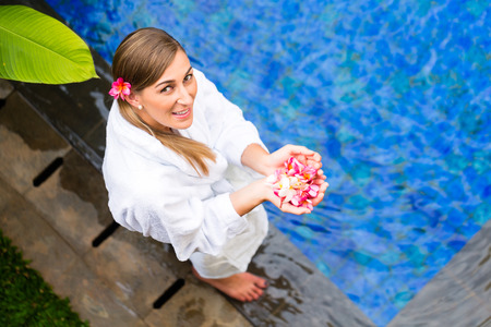 Woman with blossoms wearing bath robe at tropical wellness spa pool photo