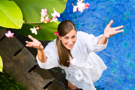 Woman throwing flower blossoms wearing bath robe at tropical wellness spa pool photo
