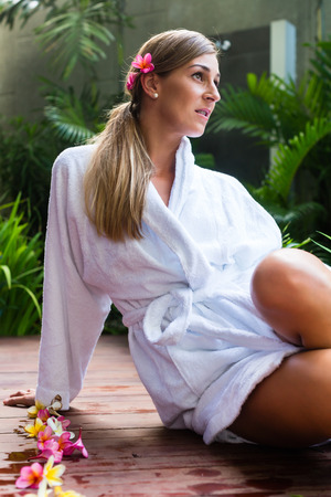 Woman with blossoms wearing bath robe at wellness spa pool photo