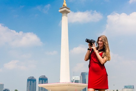 indonesia: Woman photographing while sightseeing at national monument in Jakarta, Indonesia Stock Photo