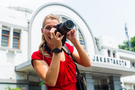 photographing: Woman photographing train station sightseeing with camera in Jakarta, Indonesia Editorial