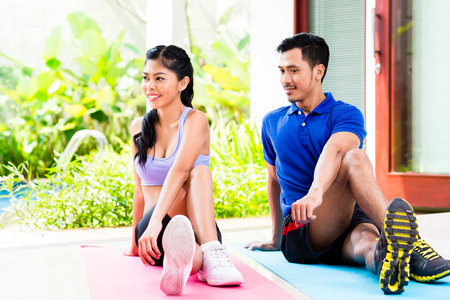 situp: Asian fitness couple doing stomach crunches in tropical home Stock Photo