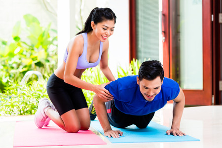 men exercising: Asian woman helping man with push-up to gain better fitness Stock Photo