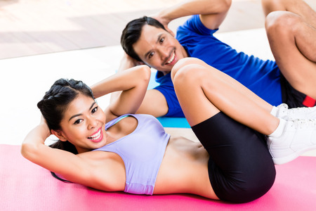 situp: Asian fitness couple, man and woman, doing sit-up in tropical home