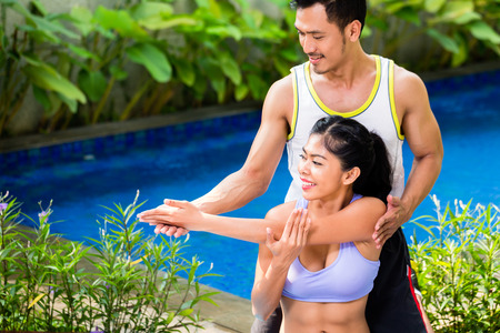 knee bend: Asian fitness couple at sport workout in tropical home