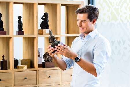 furniture store: Man at cabinet in furniture store showroom Stock Photo