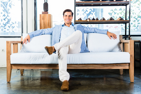 furniture store: Man sitting on couch in furniture store showroom