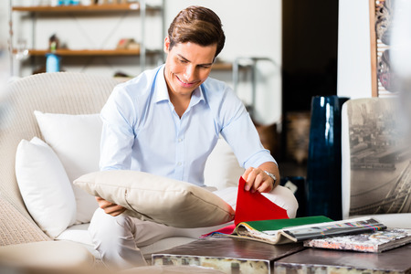 furniture store: Man choosing colors and material for furniture in store or showroom browsing through catalog