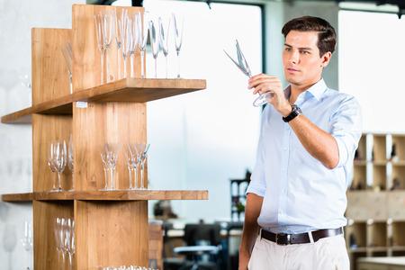 furniture store: Man in furniture store choosing glasses standing in wooden shelf