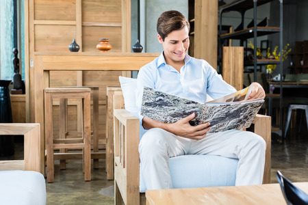 furniture store: Man in furniture store browsing catalog Stock Photo