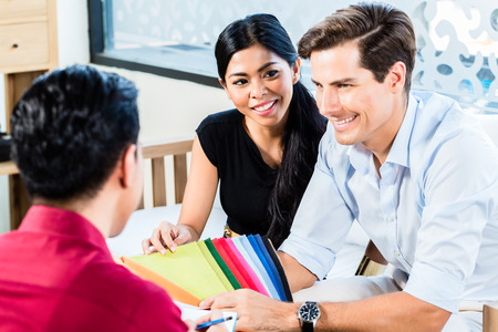 furniture store: Mixed couple in furniture store with shop assistant discussing colors and material of items they are buying Stock Photo