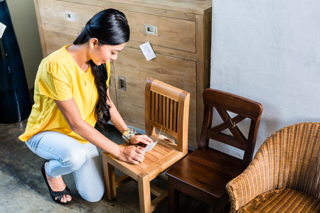 furniture store: Asian woman in furniture store buying chair