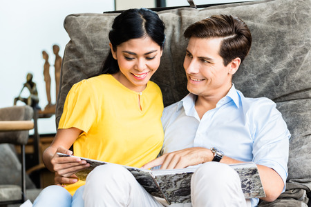furniture store: Asian Caucasian mixed couple in furniture store browsing catalog sitting in chair