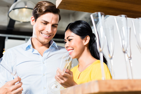 furniture store: Couple in furniture store choosing glasses, Asian woman and Caucasian man