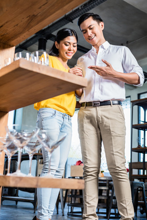 furniture store: Couple in furniture store choosing glasses, Asian woman and Caucasian man