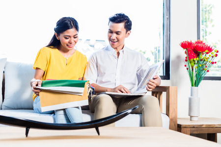 Couple in furniture store showroom choosing colors and material, Asian woman and man Stock Photo