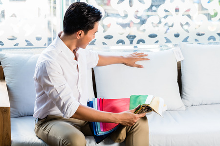 furniture store: Asian Indonesian man sitting on sofa couch in furniture store showroom with color and material catalog