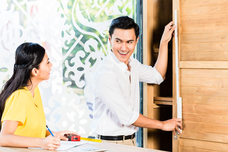 Asian couple buying cabinet in furniture store