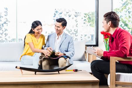 furniture store: Couple with shop assistant in Asian furniture store