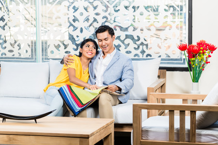 home furnishing: Asian couple buying sofa in furniture store, sitting on couch choosing color and material