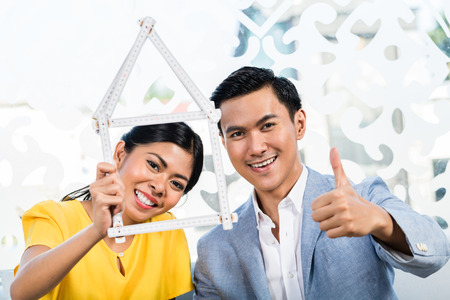 furnish: Asian couple with folding rule in furniture store