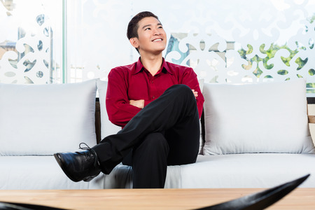 korean man: Asian Korean man sitting on sofa in furniture store