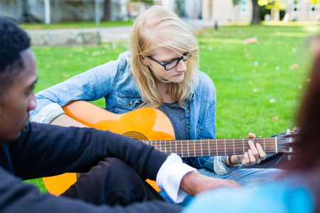 making music: Group of young people in park making music singings song and playing guitar