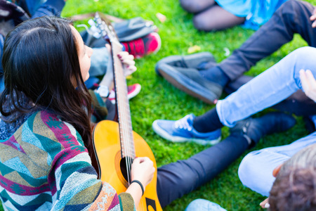 Friends singing songs in park having fun together with one girl playing the guitar, diversity group of African, Asian and Caucasian people photo