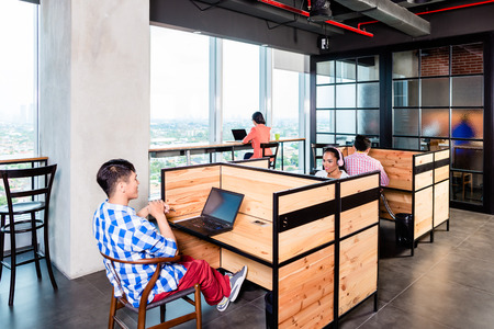 people at work: Start-up business people in coworking office working in cubicles Stock Photo