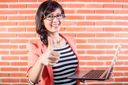 Indonesian college student with Laptop showing thumb Stockfoto