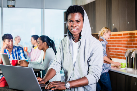 programmer: Black programmer in lounge of IT start-up coding software on his laptop, colleagues in the background