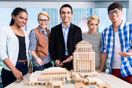 Team of architects presenting model building in presentation to customer photo
