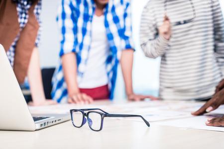 フォア グラウンドでメガネ広告の創造的な会議、焦点で代理店チーム