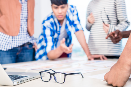 founder: Advertising agency team in creative meeting, focus on glasses in foreground Stock Photo