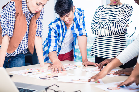 Der Werbeagentur Team Auswahl-Modell für Kampagne unter Bilder auf Tisch ausgebreitet