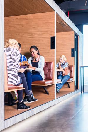 cubicle: Creative business people in coworking space having meetings in cubicle offices