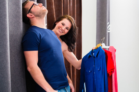 bored man: Man is bored of women trying clothes while shopping in fashion store