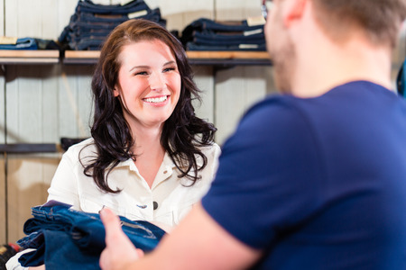 Man buying blue jeans in shop photo