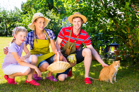 Family with cat gardening in garden photo